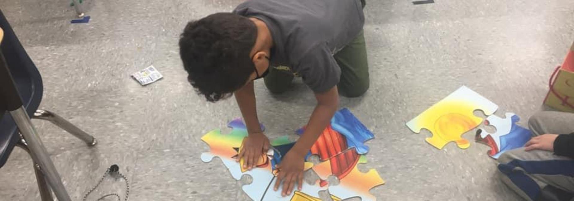 a child puts together a puzzle