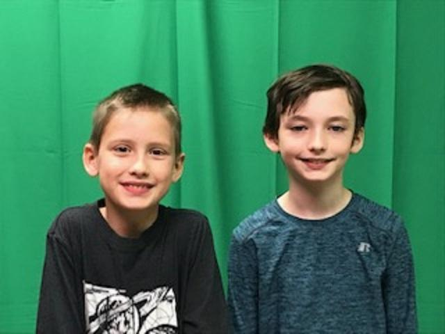 two boys standing in front of green screen