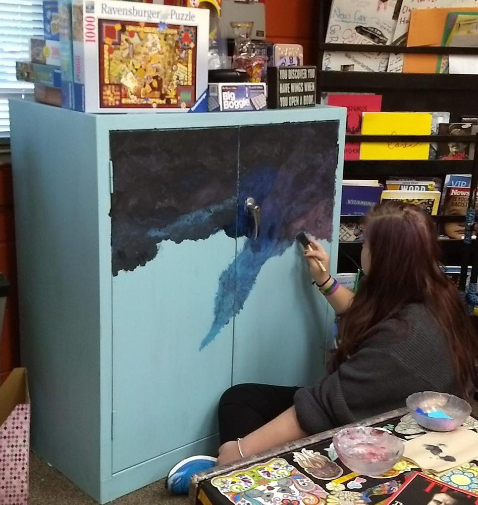 Painting a night scene on cabinet.