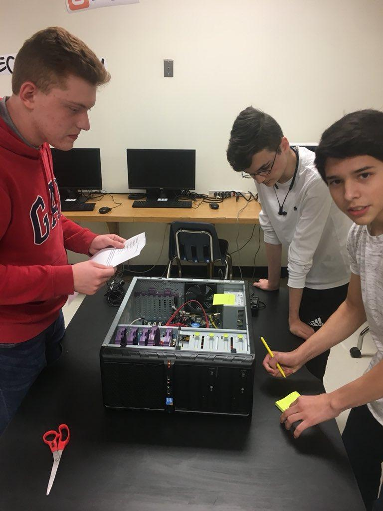 students examining insides of a computer