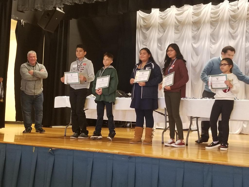 uhms students on stage with their certificates with mr. sanchez and hurtado