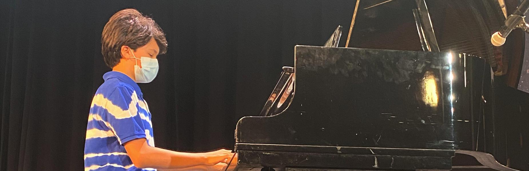 Photo of student playing the piano on Fine Arts Day