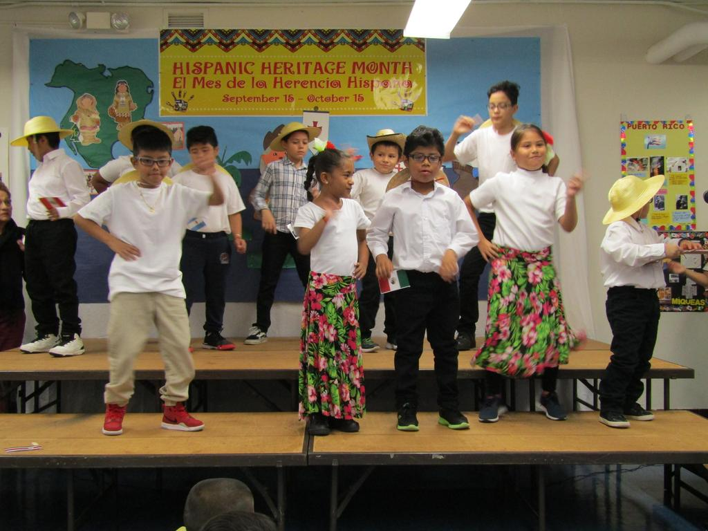a group of children on the stage dancing and singing