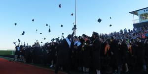 Members of the TKHS Class of 2019 toss their caps into the air.