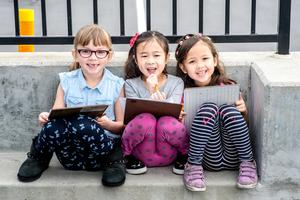 Three students posing for a picture with their devices in their hands.