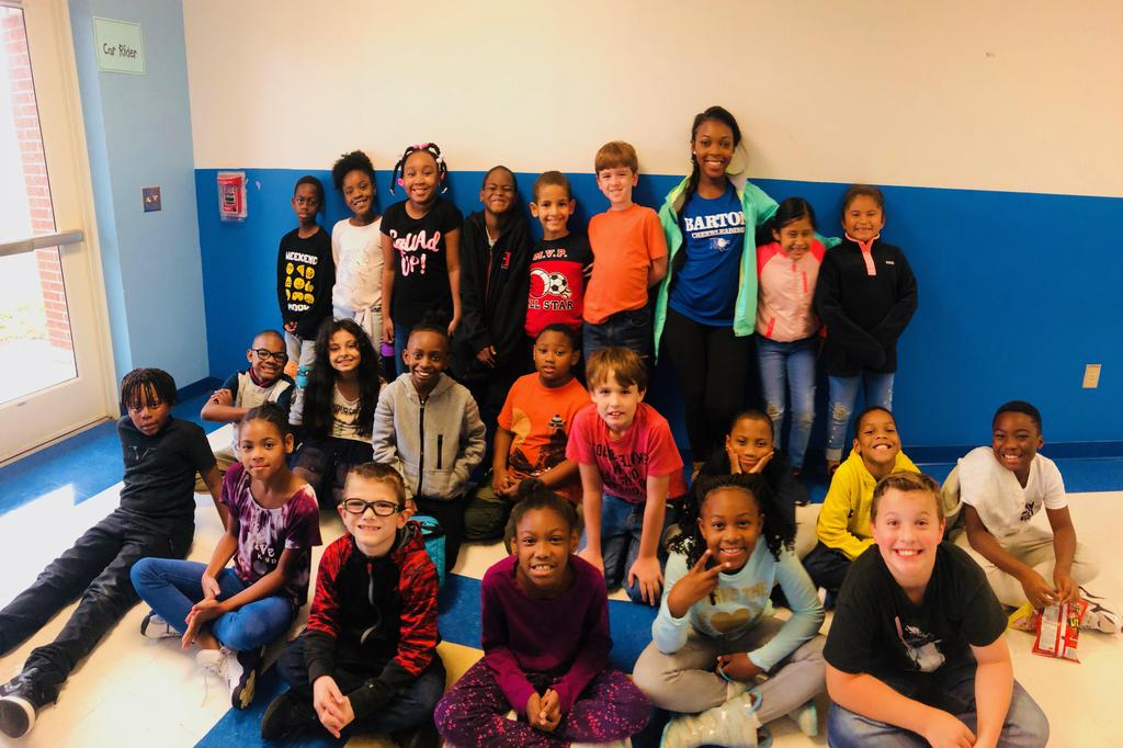 Barton College students has photo taken with Mrs. Watson's third grade class.