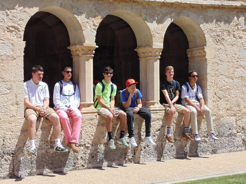 Students sitting on a wall in Spain