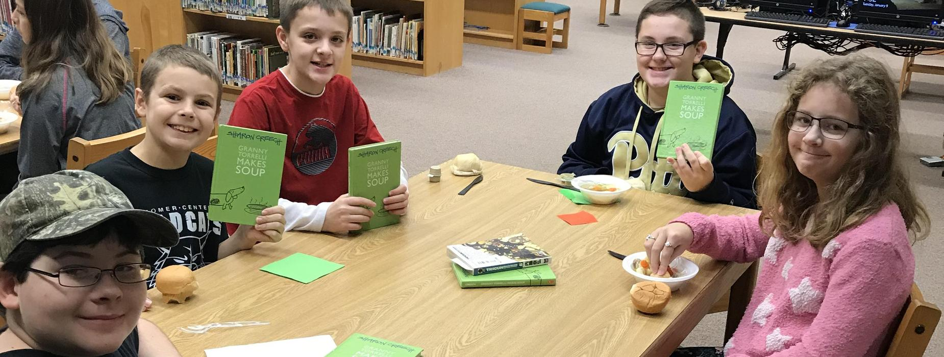 Several elementary students sitting at a table in the library with food as part of the Breakfast Book Club.