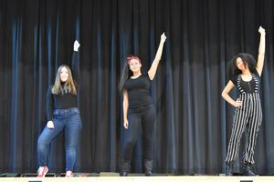 Three girls in black on stage