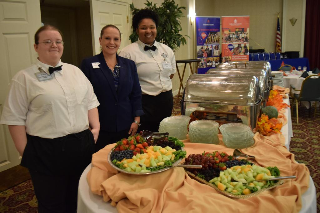 staff smiling next to buffet