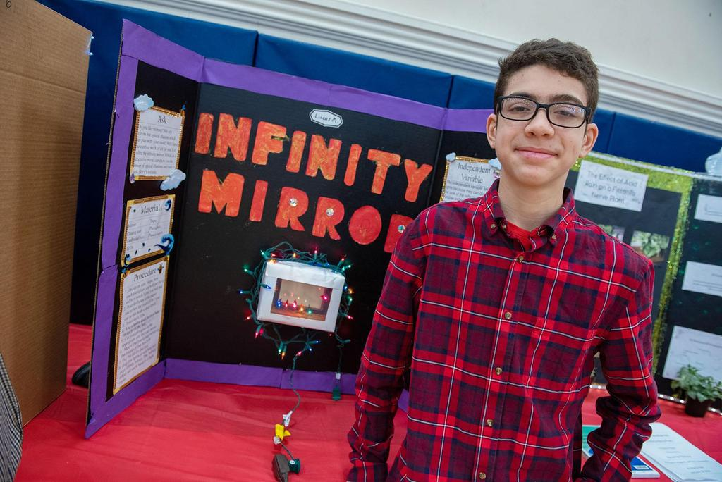 A student stands in front of his project called Infinity Mirror