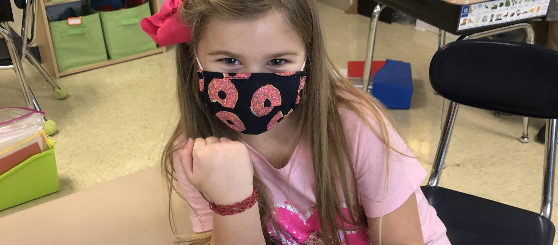 girl wearing a mask showing off her bracelet