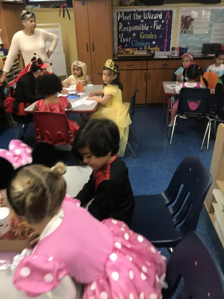kids seated at tables in group of four playing various halloween games with the high school students