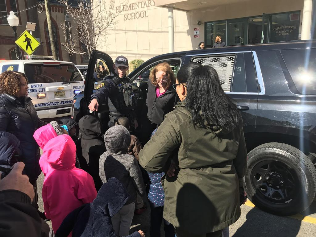 principal inside the drivers seat of the canine vehicle with officer explaining to the children the special parts of the car