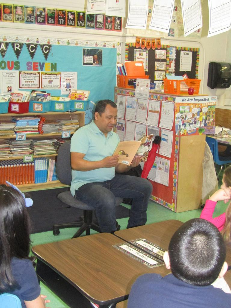 3rd grade class listening to parent volunteer read the class a story