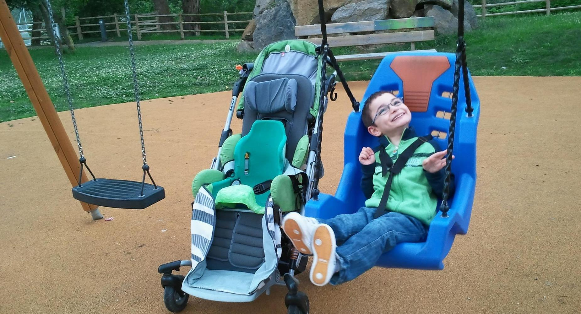 smiling boy swinging in an adapted swing next to his wheelchair