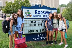 Five students pose in front of Roosevelt Intermediate School sign during first week of school.