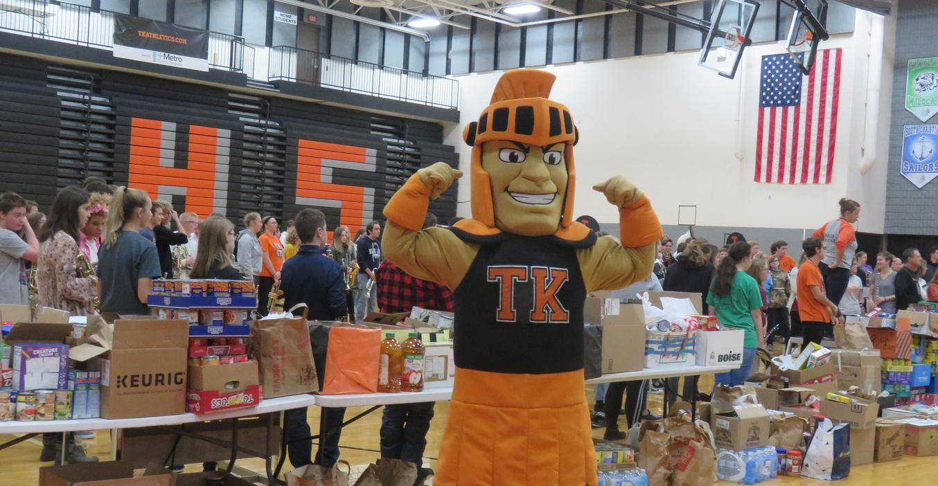 The TK Trojan flexes his muscles as students donated food items for food pantries.