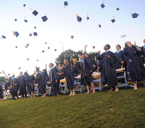 graduates throwing caps in the air