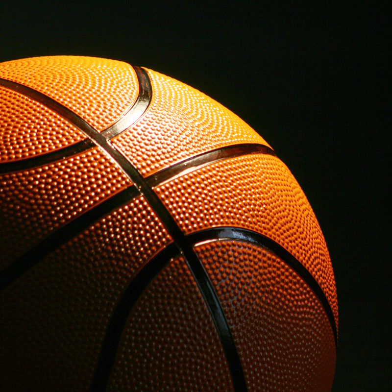 A close up of a basketball set against a black backdrop