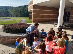 Mr. Allender and class of students sitting outside