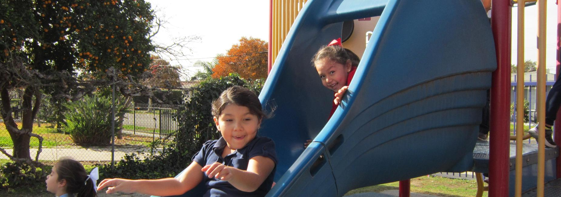 Students on the slide during kindergarten recess.