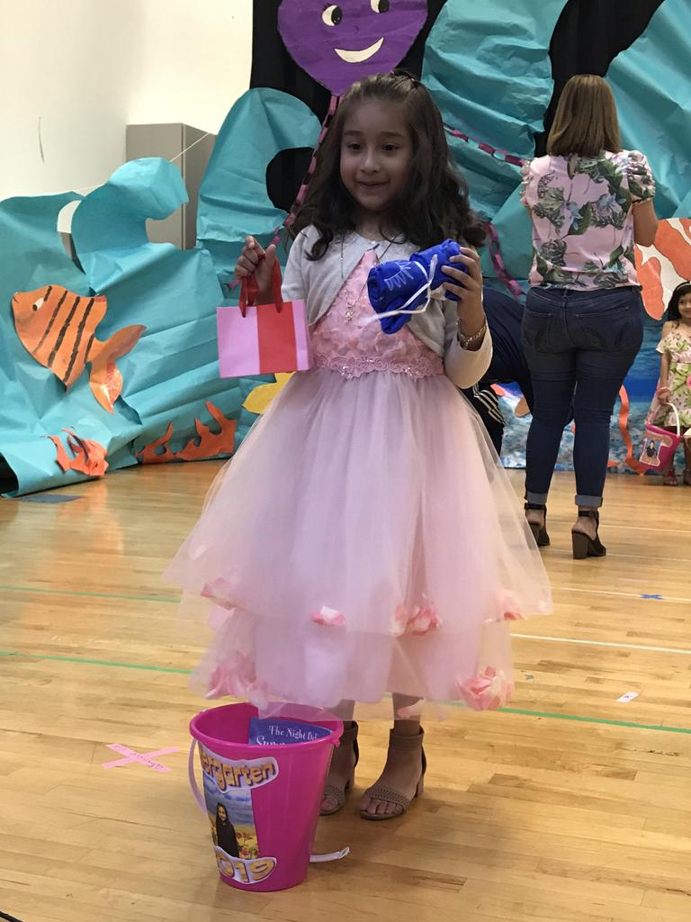 girl with pretty dress showing off the items in her summer bucket