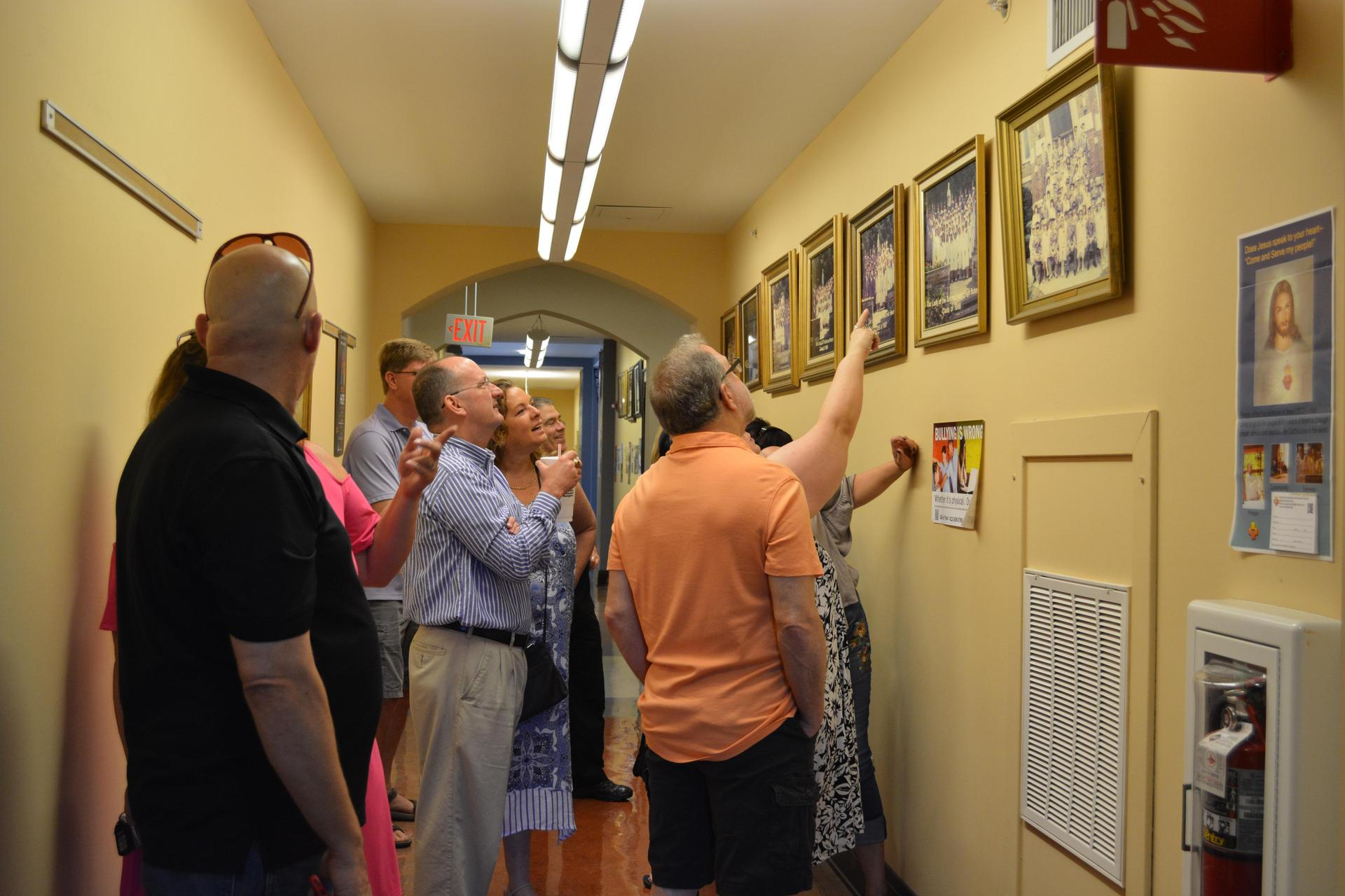 Alumni visiting the school check out their graduation photo hanging in the hall