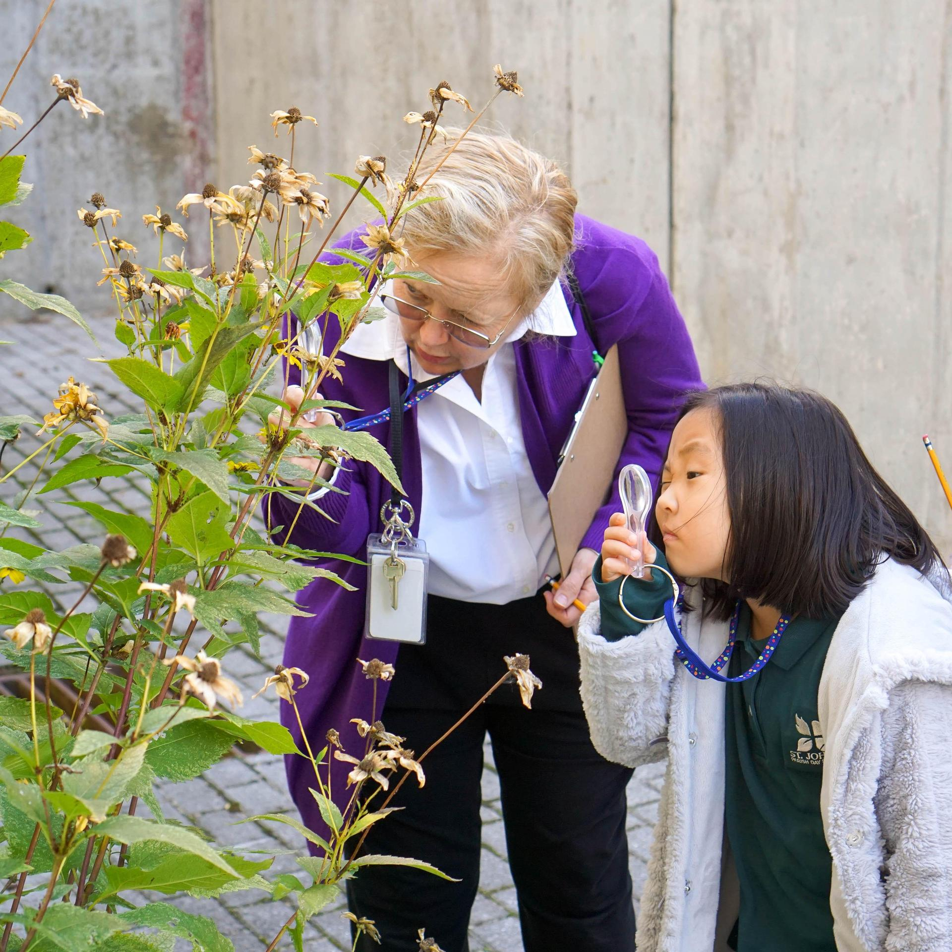 student and teacher observing a plant