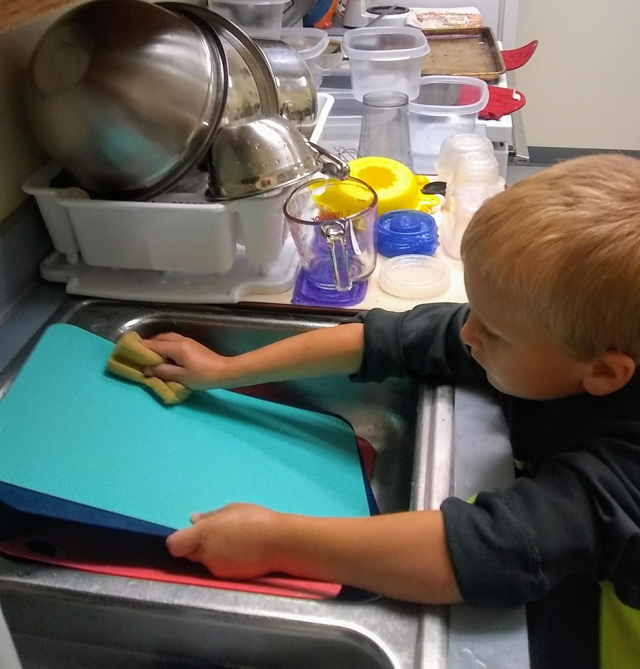 a child washing dishes