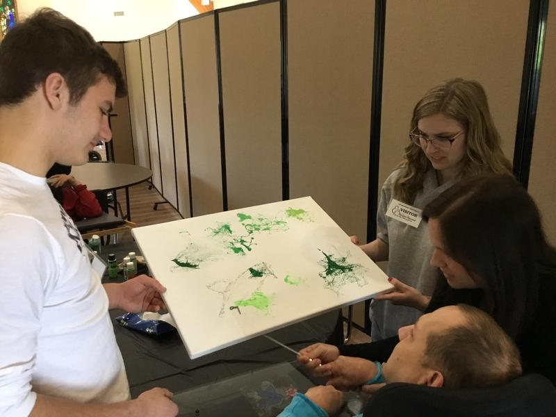 photo of OLSH students helping a resident at McGuire Memorial with an art project