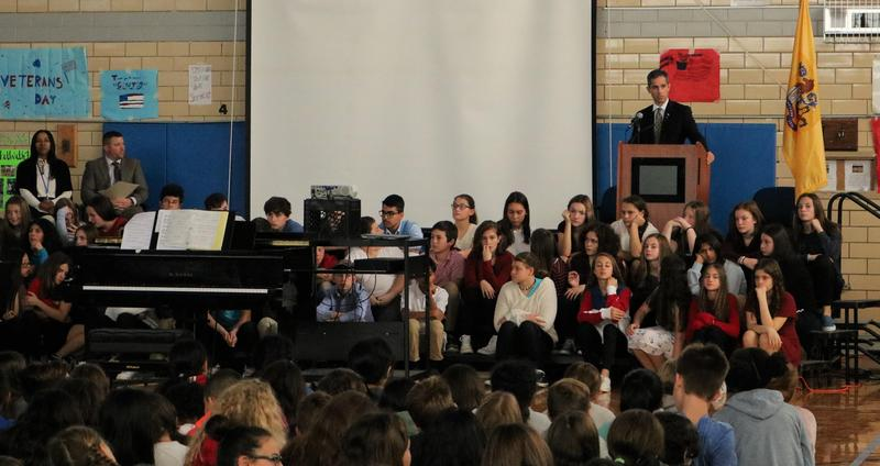 Photo of EIS teacher and veteran speaking at Veteran's Day assembly.