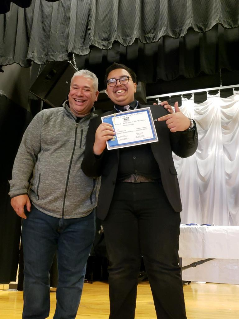 mr. sanchez and uhms male student on stage with his winning certificate