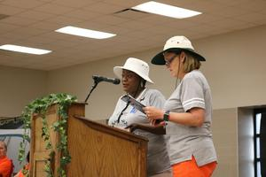 Two women at podium wearing hats