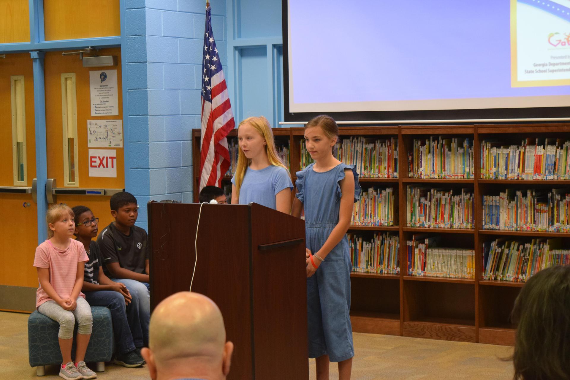 students presenting at podium