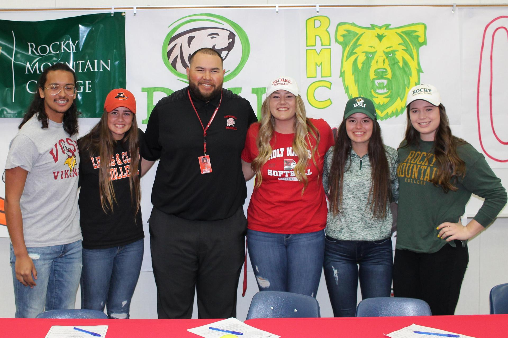 Isaac Salazar, Kylie Hill, Morgan Sewell, Claire Wright and Kelsey Volkmar are prepared to sign college letters of intent with Athletic Director Jordan Murphy.