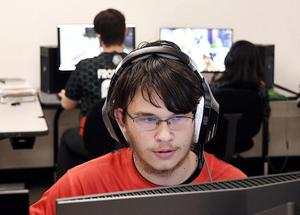 student with headphones looking at computer screen, courtesy of Anderson Herald Bulletin