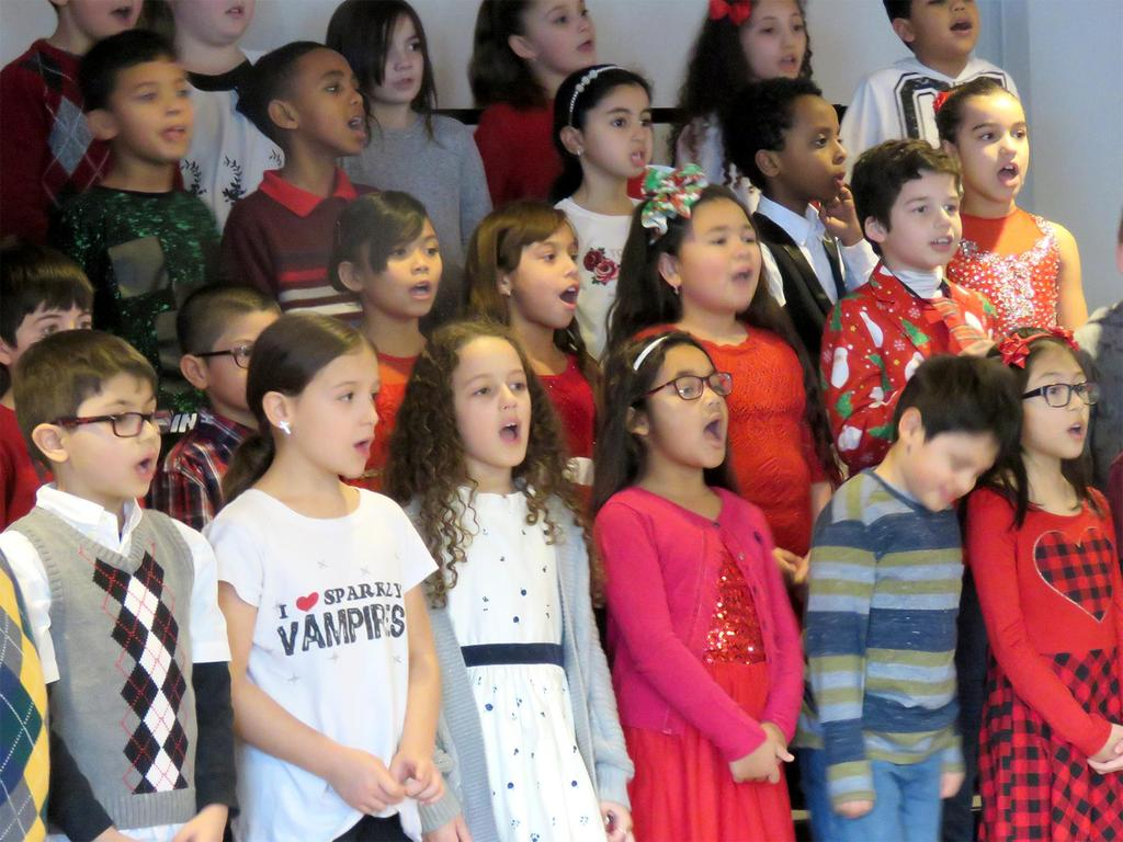 A close-up of a section of a stage full of students singing