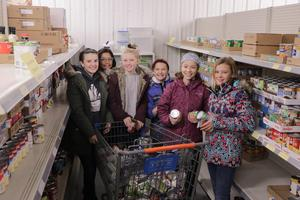 Students smile at the camera while stocking shelves at Christian Neighbors.