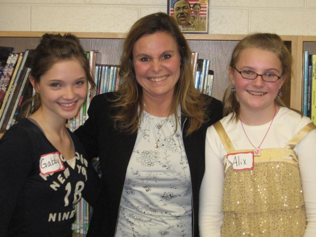principal poses with two students