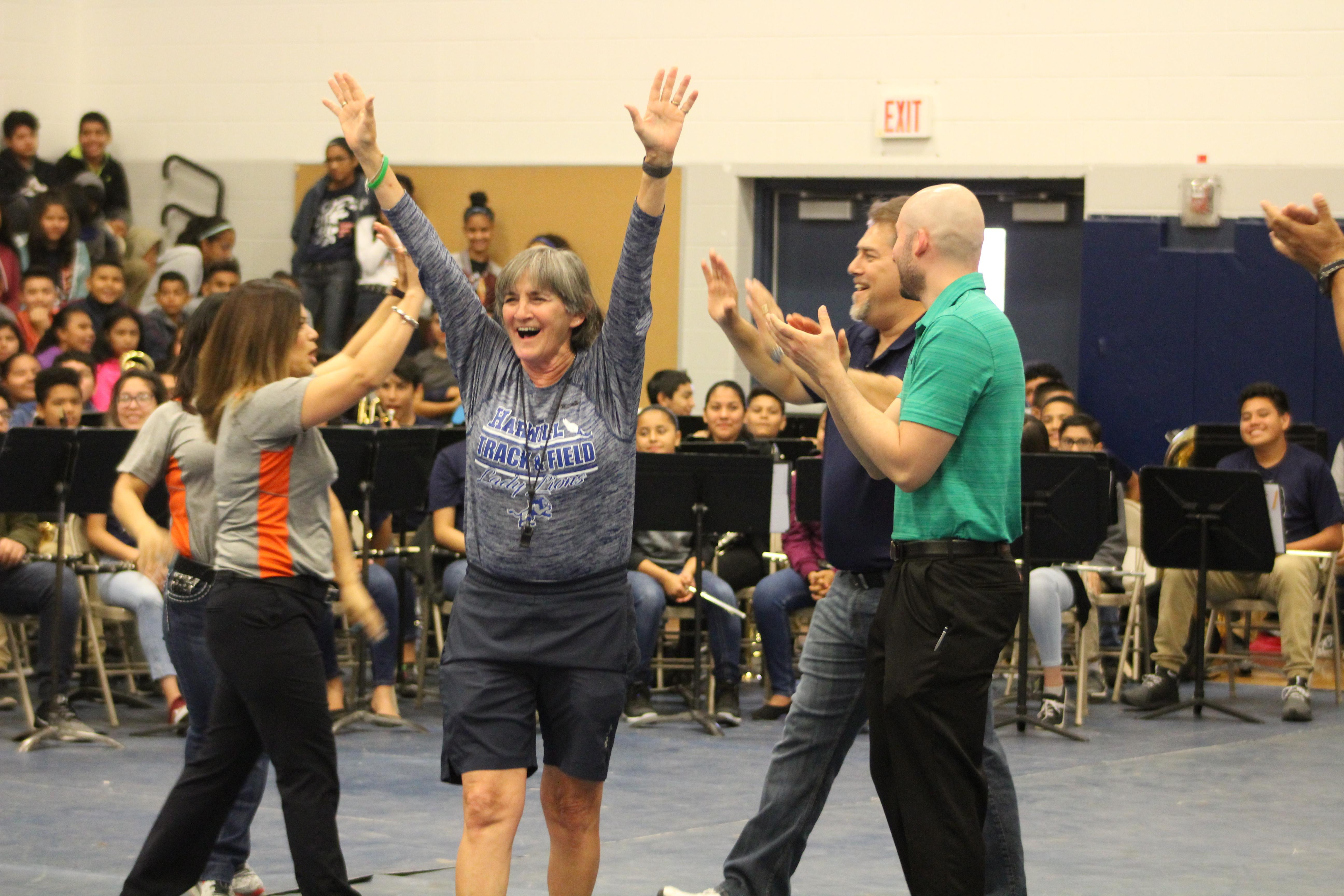 Teachers celebrate during a school pep rally