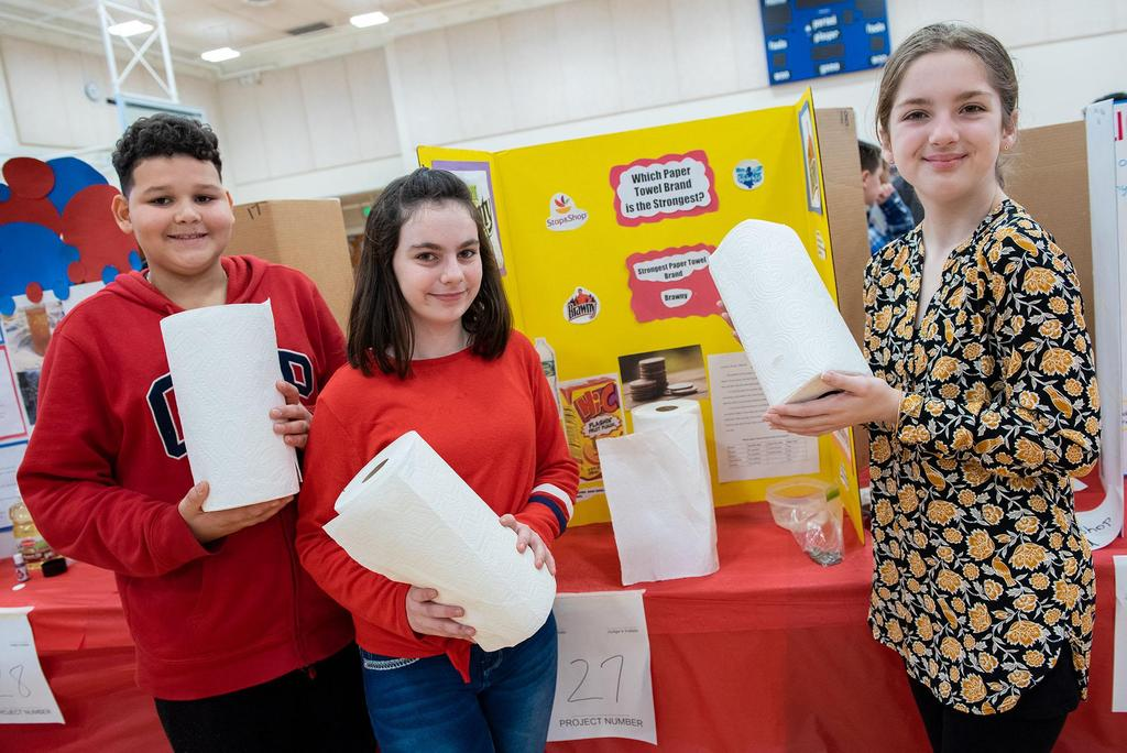 Three students hold rolls of paper towels