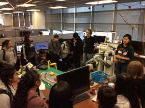 students watching two presenters and a robot in a technology research room