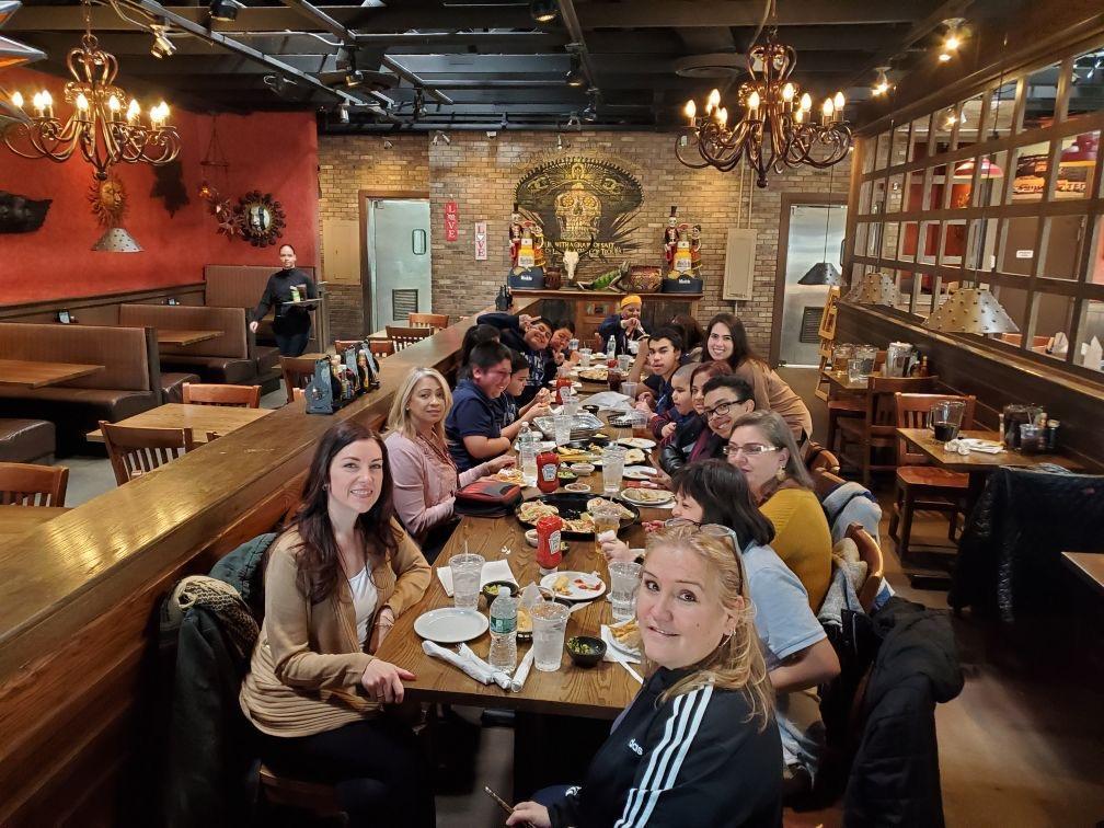 group photo of teachers and students enjoying food