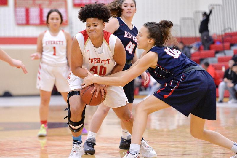 A defender tries to take the basketball from the clutches of an Everett player