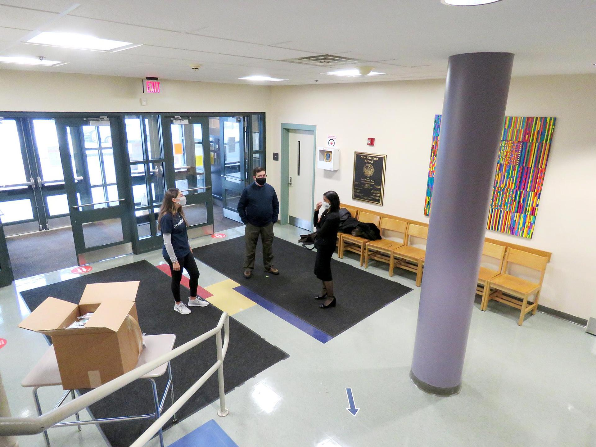 Overhead view of three people talking informally in the Keverian School lobby