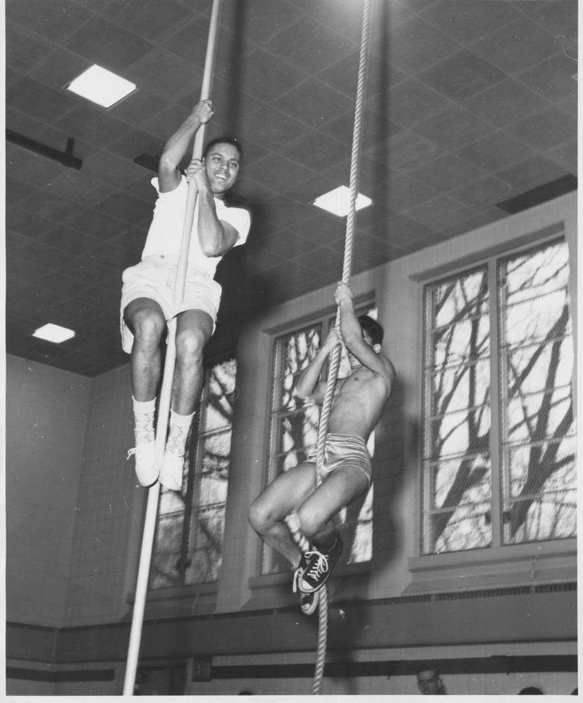 Two students climbing a rip to the gym ceiling