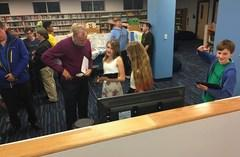 Students explain their Titan alien cell projects in the GTMS library for Expo night.
