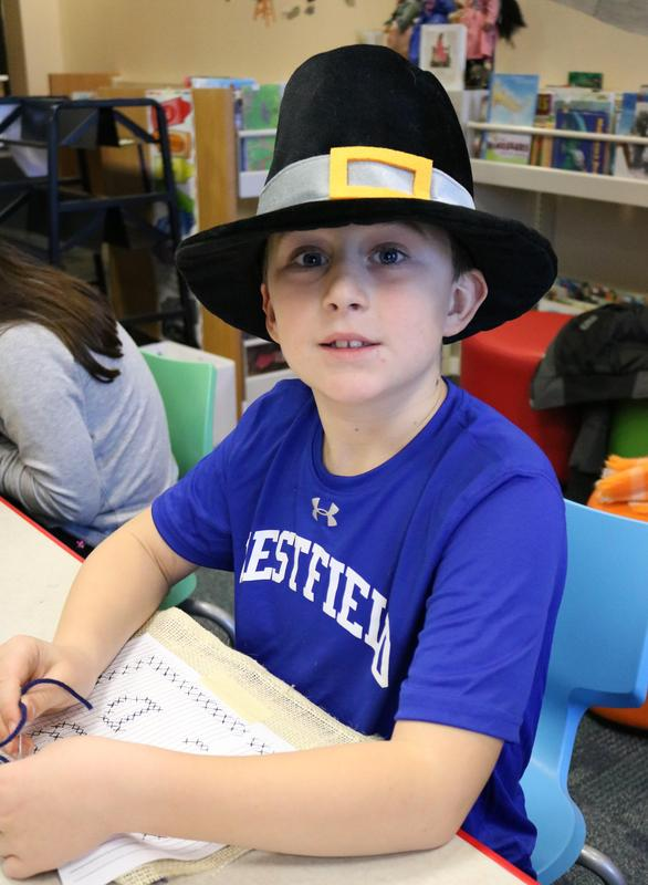 2nd grader, wearing colonial era hat, sews needlepoint sampler during Colonial Days at Wilson School.