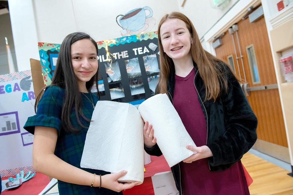 Two students hold rolls of paper towels